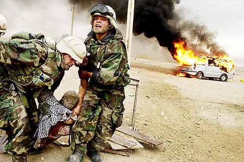 U.S. Marines save an Iraqi civilian from his burning vehicle during the Iraq War invasion of 2003.