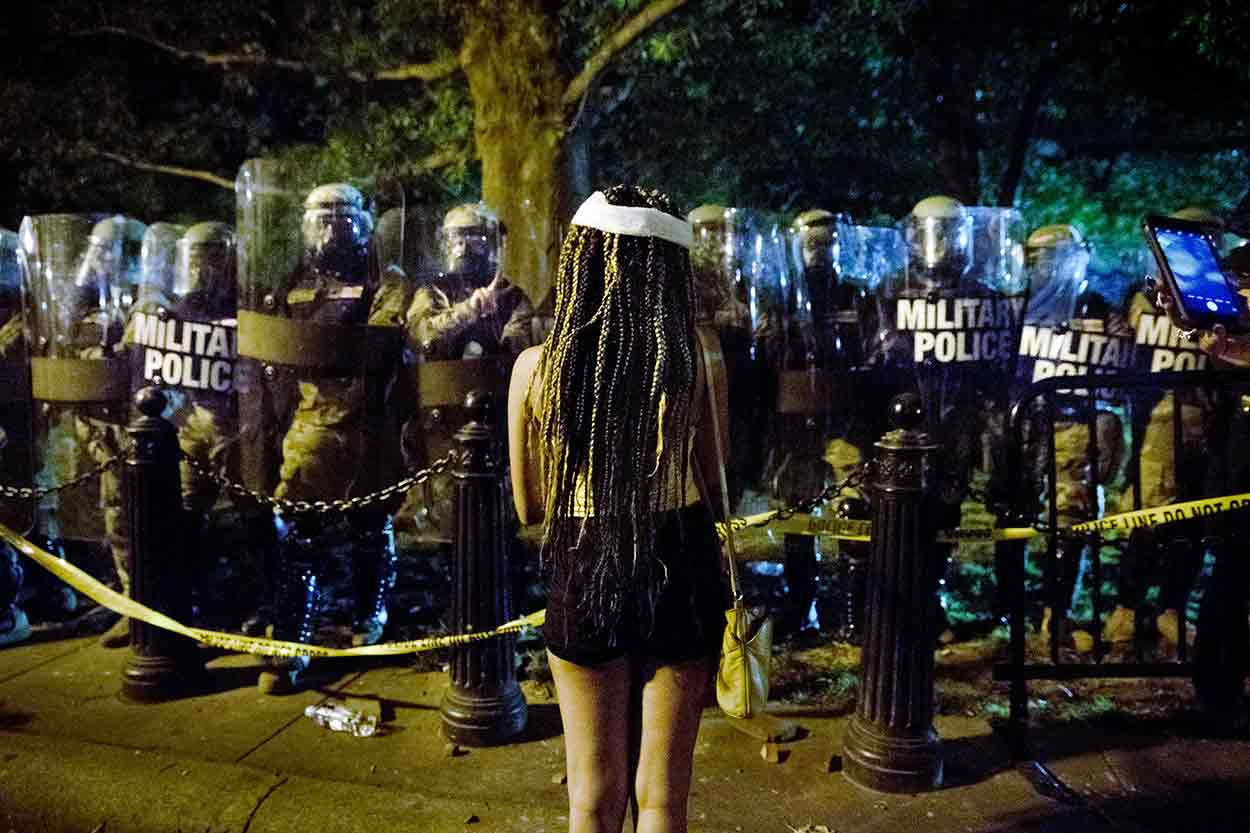A woman with a bandage on her head faces a line of police carrying shields during George Floyd protests in Washington, DC.