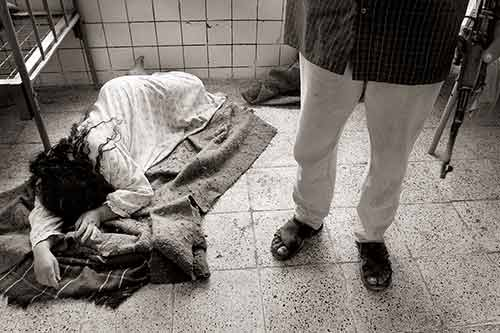 A female mental patient in a nightgown who earlier showed signs of agitation and anger lays on blankets on the floor while a guard armed with an AK-47 stands nearby.