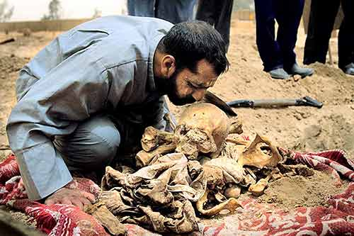 Iraqi man kissing the skull of his long deceased brother who was killed by Saddam Hussein's regime, at Abu Ghraib cemetery in Baghdad, Iraq.