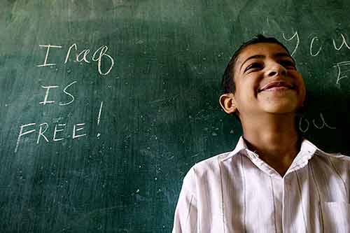 """Young Iraqi boy smiling by a chalkboard where American soldiers left a message, """"Iraq Is Free!"""""""