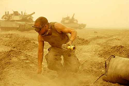 U.S. Marine Brian Flaherty of New York works on a tank bladder in a dust storm during the Iraq War.