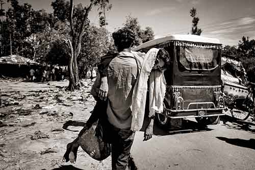 A Rohingya refugee man carries his unconscious wife to an auto rickshaw as they arrive to Bangladesh from Myanmar.