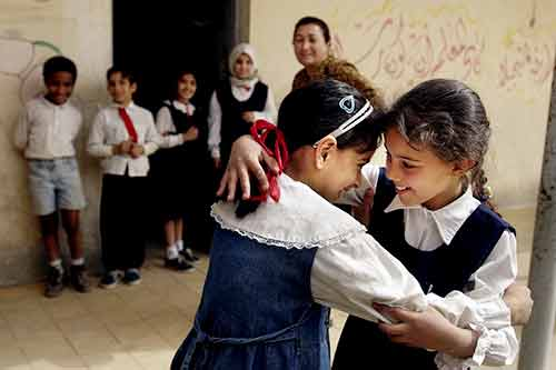 After not having seen each other for weeks during the war, Fatma Mohammad and Zubaida Salman hug each other fondly on the first day of their school reopening.